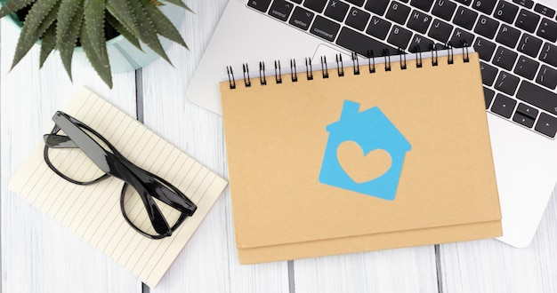Huisbeeldje op een notitieboekje met een bril en een laptop. creatieve platliggende compositie.