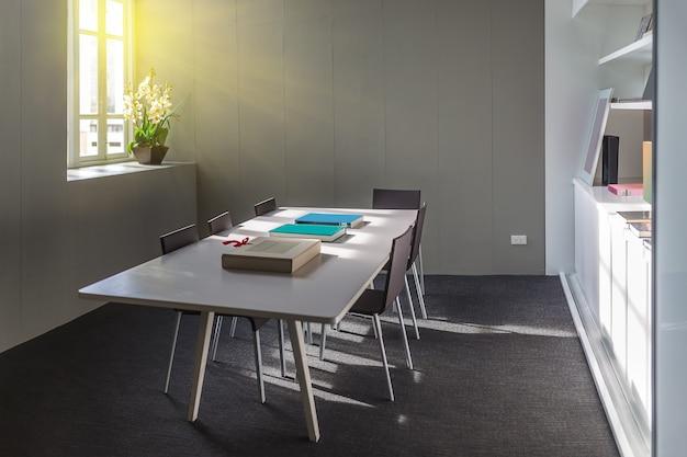 Huisbibliotheek met boekenplanken en een witte tafel, vijf stoelen.