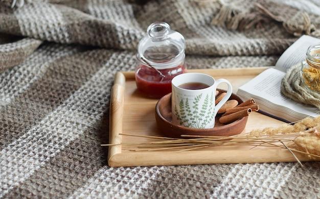 Huisbinnenland van woonkamer. wollen deken en een kopje thee met stoom. ontbijten op de bank in de ochtendzon. gezellig herfst- of winterconcept.