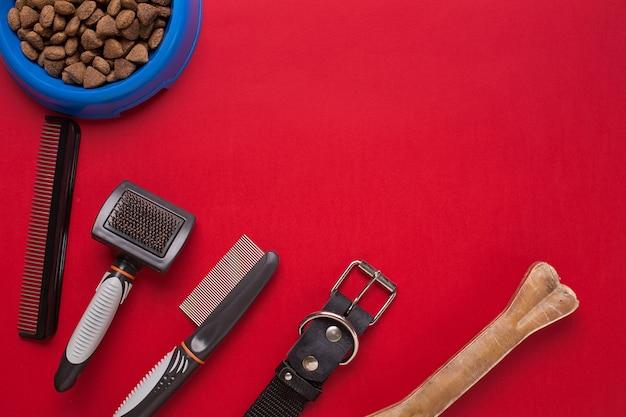 Huisdier accessoires op rode achtergrond. bovenaanzicht. stilleven. ruimte kopiëren
