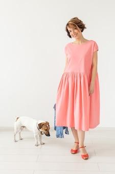 Huisdier en mensen concept - jonge vrouw in roze jurk met jack russell over de witte muur