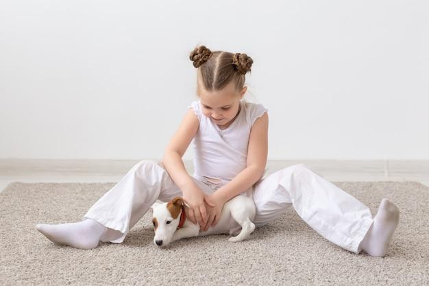 Huisdier, kinderen en dier concept - glimlachend kind meisje zit met puppy jack russell terrier.