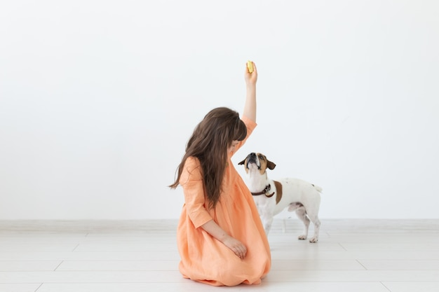 Huisdier, kinderen en honden concept - klein meisje in jurk spelen met puppy