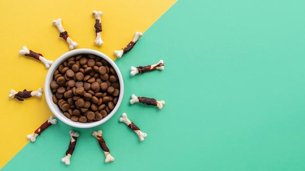 Huisdieraccessoires stilleven met voerbak en veel kauwbotten voor honden