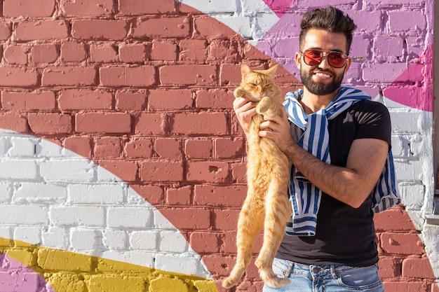 Huisdiereigenaar en vriendschapsconcept - knappe arabische man houdt een schattige gemberkat vast en knuffelt hem. kat met nieuwsgierige uitdrukking
