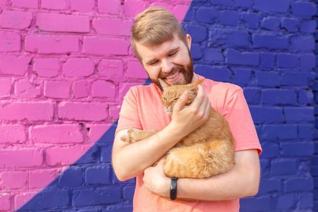Huisdiereigenaar en vriendschapsconcept - knappe man houdt en knuffelt schattige gemberkat. kat met nieuwsgierige uitdrukking.
