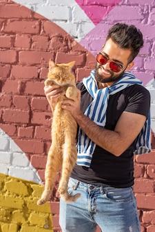 Huisdieren en dieren concept - knappe jongeman met schattige rode kat buitenshuis