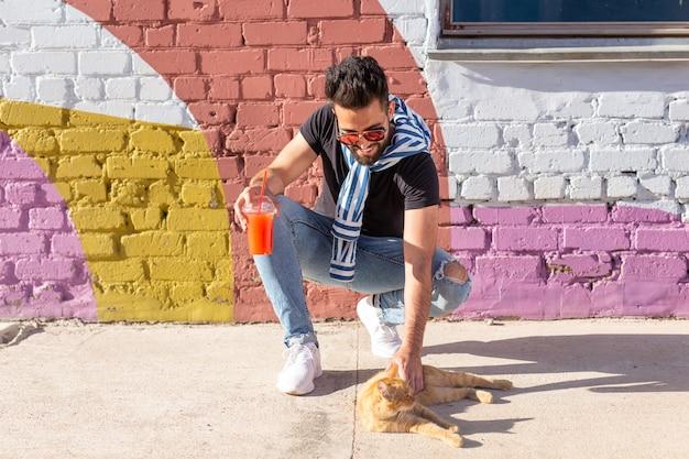 Huisdieren en dieren concept - knappe jongeman speelt met schattige rode kat buitenshuis