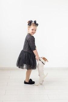 Huisdieren en dierlijk concept - kindmeisje dat met puppy jack russell terrier speelt.