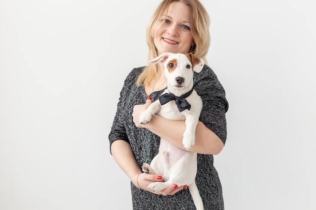 Huisdieren en dierlijk concept - mooie vrouw met puppy jack russell terrier op witte achtergrond met copyspace