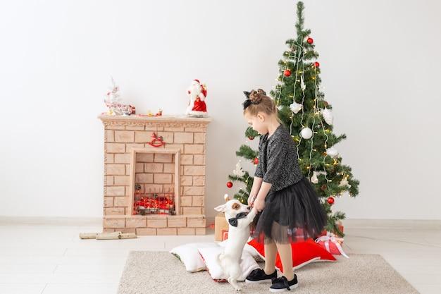 Huisdieren, vakantie en kerstmisconcept - kindmeisje dat met puppy jack russell terrier speelt dichtbij kerstboom.