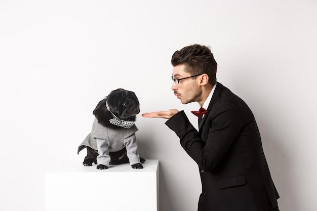 Huisdieren, wintervakanties en feestconcept. knappe jonge man lucht kus verzenden naar schattige zwarte puppy kostuum dragen voor nieuwjaar, eigenaar permanent in pak over wit.