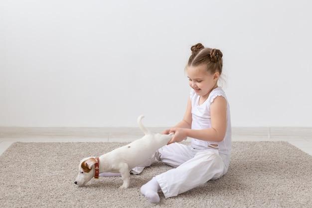 Huisdierenkinderen en dierlijk conceptkindmeisje die een puppy bij de poten houden