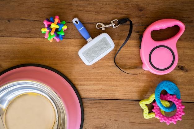 Huisdierenriemen en rubberstuk speelgoed op houten achtergrond.
