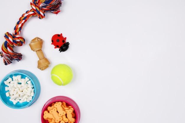 Huisdierentoebehoren, voedsel en stuk speelgoed op witte achtergrond. plat leggen. bovenaanzicht.