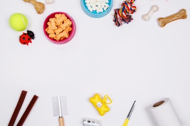 Huisdierentoebehoren, voedsel en stuk speelgoed op witte achtergrond