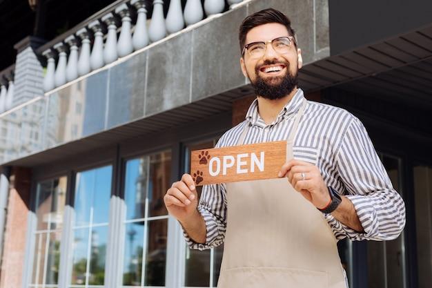 Huisdiervriendelijke plek. opgetogen gelukkige man die lacht terwijl hij een nieuw huisdiervriendelijk café opent