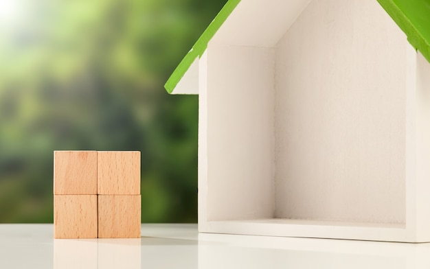 Huisdoosmodel en houten kubussen op een wit oppervlak - onroerend goed bedrijfsconcept