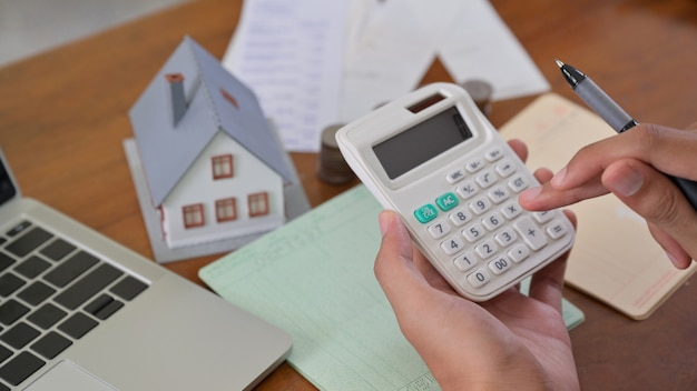 Huiseigenaar gebruikt rekenmachine om huiskosten te controleren.