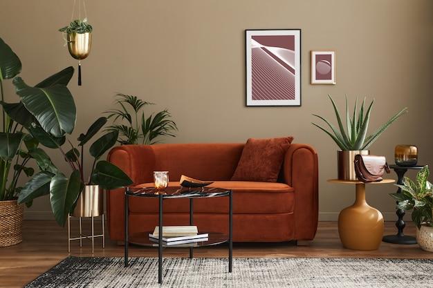 Huiselijk interieur van woonkamer met designbank, mock-up posterframes, veel planten, salontafel, kamerscherm en elegante persoonlijke accessoires in modern interieur. sjabloon.