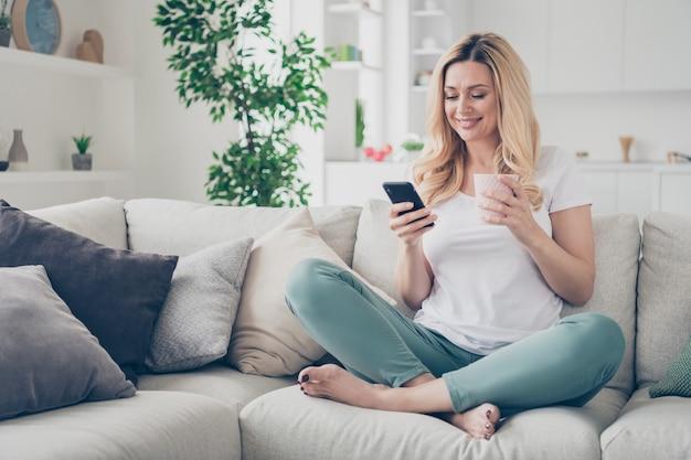 Huiselijk mooie vrolijke dame ontspannen zitten bank browsen telefoon houden mok