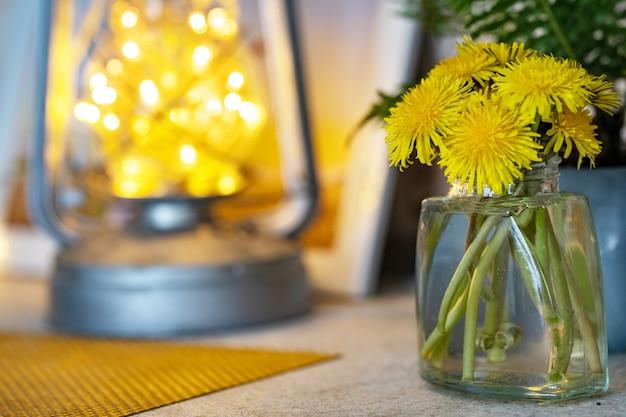 Huiselijke sfeer, op tafel staat een glazen pot met een boeket paardebloemen
