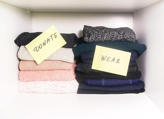 Huisgarderobe met verschillende kledingstukken. seizoensgebonden kleding sorteren voor donatie. kleine ruimte organisatie.
