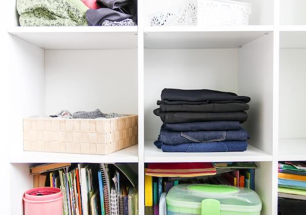 Huisgarderobe met verschillende kleren. kleine ruimte organisatie. het contrast van orde en wanorde. verticale opslag.