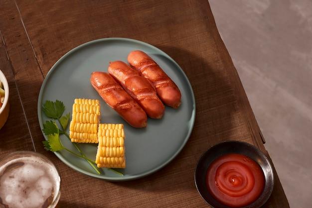 Huisgegrilde worstjes op een donkere plaat, een vleesgerecht op een donkere houten tafel, warme worstjes met kruiden en zout in een huiskeuken, kopieerruimte, rustieke stijl, kunst