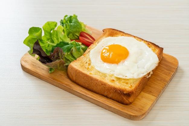 Huisgemaakt brood geroosterd met kaas en gebakken ei bovenop met groentesalade als ontbijt