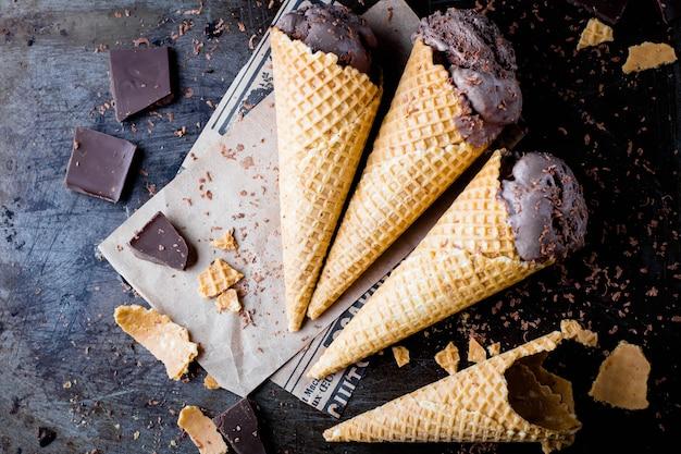 Huisgemaakt chocolade-ijs in wafel kegels op donkere metalen achtergrond. zomer dessert. bovenaanzicht