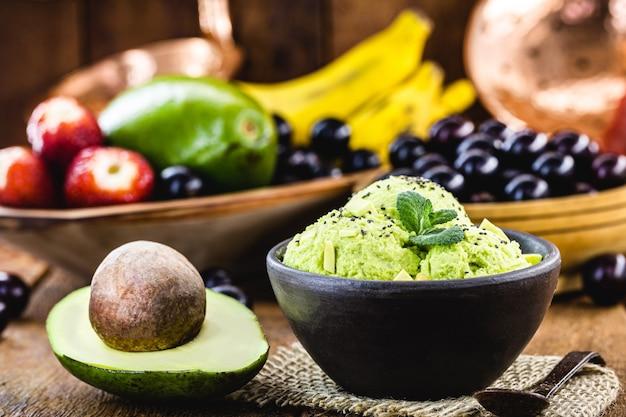 Huisgemaakt en vegan avocado-ijs gemaakt zonder melk, met fruit op de achtergrond
