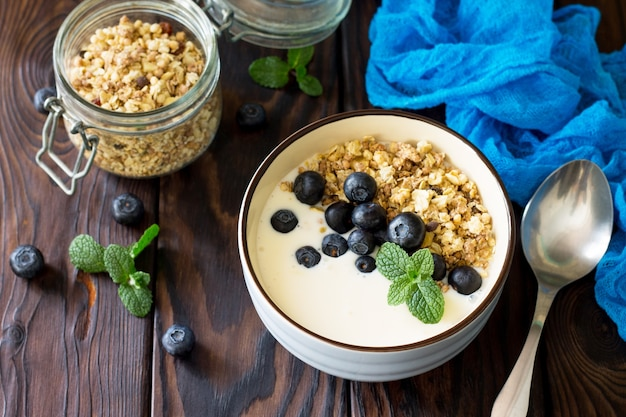 Huisgemaakt gezond ontbijt in een kom met huisgemaakte gebakken granola verse bosbessen en yoghurt