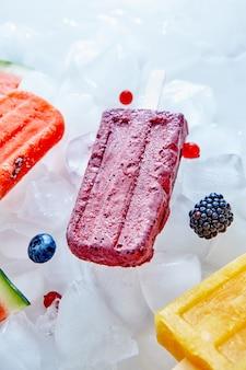 Huisgemaakt ijs op een stokje met een stuk fruit