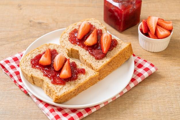Huisgemaakt volkorenbrood met aardbeienjam en verse aardbeien