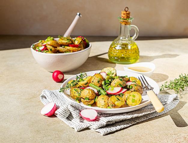 Huisgemaakte aardappelsalade met sperziebonen, radijsjes en kruiden.