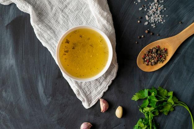 Huisgemaakte boullion of heldere soep in een keramische kom in de keuken, gezonde voeding en diëten