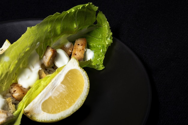 Huisgemaakte caesarsalade met kip, sla, citroen, toast, cesarsaus, kaas en knoflook