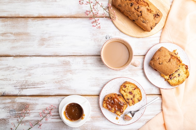 Huisgemaakte cake met rozijnen, amandelen, zachte karamel en een kopje koffie op een witte houten ondergrond en oranje linnen textiel