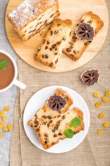 Huisgemaakte cake met rozijnen, gedroogde persimmon en een kop warme chocolademelk op een grijze betonnen tafel en linnen textiel. bovenaanzicht, plat leggen, close-up.