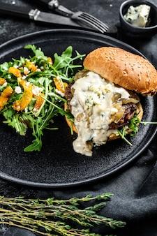 Huisgemaakte cheeseburger met blauwe kaas, spek, gemarmerd rundvlees en uienmarmelade, een bijgerecht van salade met rucola en sinaasappels. zwart oppervlak. bovenaanzicht