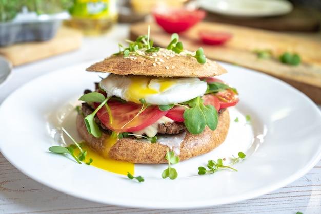 Huisgemaakte cheeseburger van rundvlees met volkorenbroodjes en gepocheerd ei