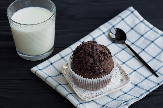 Huisgemaakte chocolademuffins of cake met een glas melk