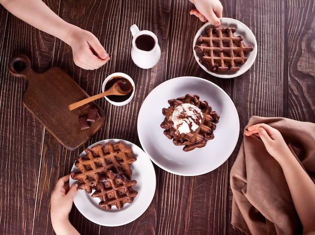 Huisgemaakte chocoladewafels met roomijs versierd chocoladesiroop