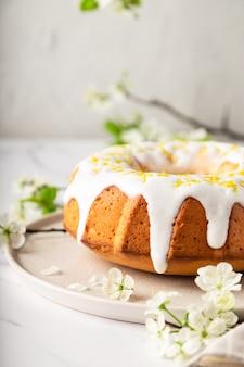 Huisgemaakte citroen bundt cake gedecoreerd met wit glazuur en schil