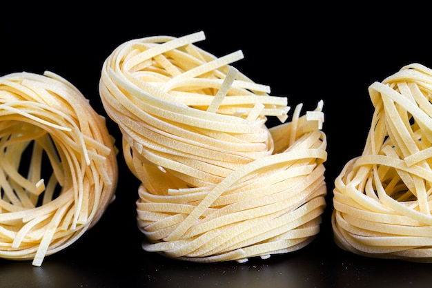 Huisgemaakte echte pasta op een zwarte achtergrond, niet gekookt in een rauwe vorm tijdens hun opslag