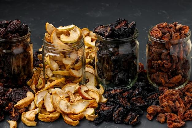 Huisgemaakte gedroogde appels, pruimen, peren en abrikozen in glazen potten