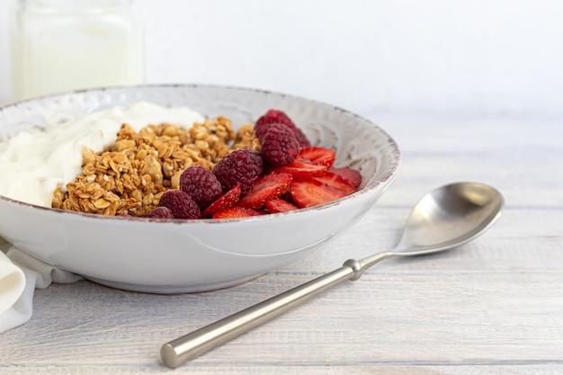 Huisgemaakte granola met aardbeiplakken en yoghurt