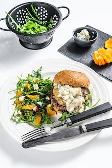 Huisgemaakte hamburger met blauwe kaas, gemarmerd rundvlees en uienmarmelade, een bijgerecht van salade met rucola en sinaasappels