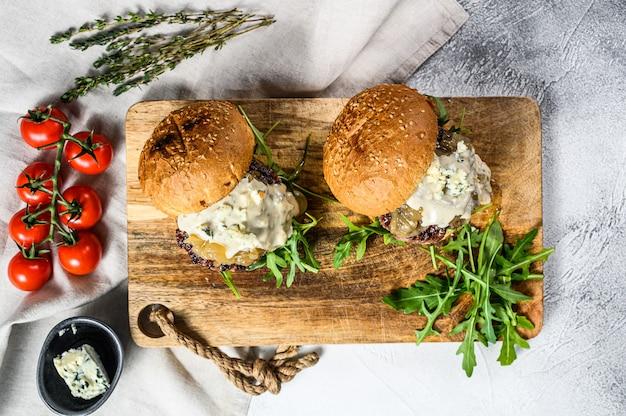 Huisgemaakte hamburger met blauwe kaas, gemarmerd rundvlees, uienmarmelade en rucola. grijs oppervlak. bovenaanzicht
